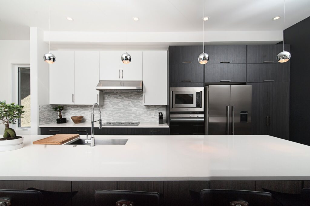 Contemporary kitchen with white quartz countertops and dark wood cabinetry